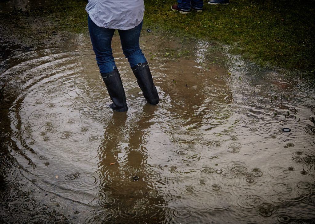 Image shows a person from the waist down, wearing a white shirt, jeans, and rain boots. The person is standing in a large puddle of water.